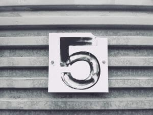 a sign displaying the number 5 on a metal door