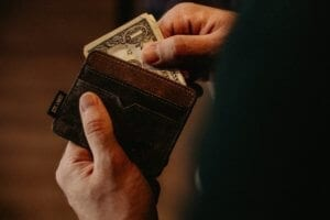 a closeup photo of a person pulling dollar bills from a wallet