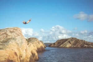 man diving off a cliff into water