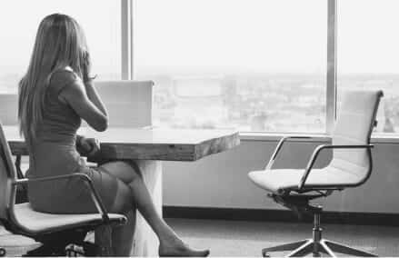 a woman on the phone at a conference room table looking out the window