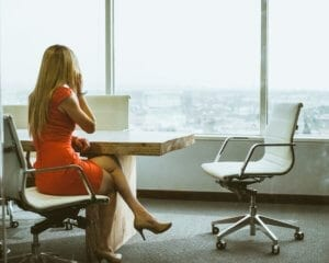 woman sitting in a chair at a conference table making a sales call