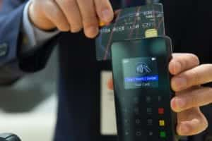 A man scanning a credit card through a card reading machine