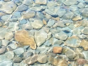 a clear pool of water with rocks at the bottom to represent clarity of vision
